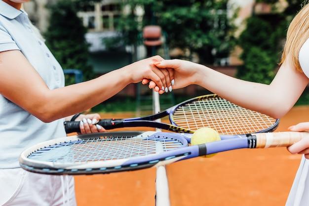 Nahaufnahmefoto. übergibt die mädchen, die hände auf tennisplatz, team rütteln. zusammen arbeiten und spielen.