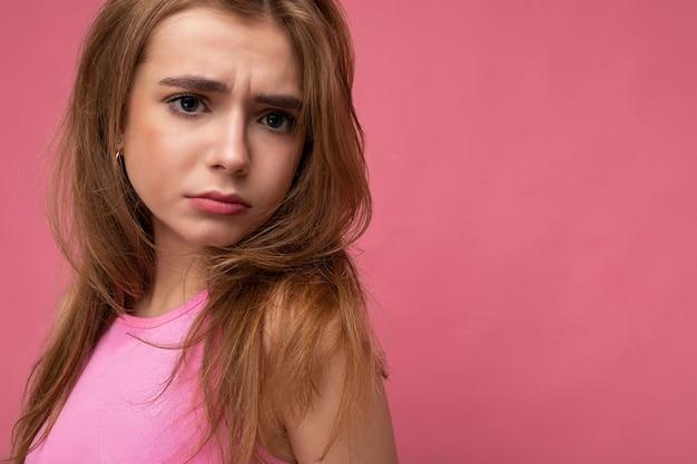 Nahaufnahmefoto unzufriedener trauriger junger schöner dunkelblonder weiblicher person mit aufrichtigen gefühlen einzeln auf hintergrundwand mit kopienraum, die stilvolle rosa spitze trägt. negatives konzept.