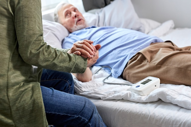 Nahaufnahmefoto von älteren paarhänden, die zusammenhalten, frau unterstützt ihren kranken ehemann, der auf bett im krankenhaus liegt