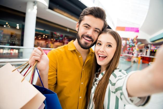 Nahaufnahmefoto von attraktiven lustigen dame, gutaussehendem mannpaar, das einkaufszentrum besucht, trägt zusammen viele taschen, die selfies machen, gute laune tragen lässiges hemd-outfit drinnen