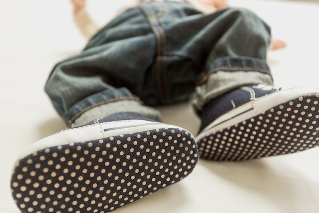 Nahaufnahmefoto von babyfüßen in jeans und turnschuhen