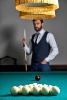 Nahaufnahmefoto von billardkugeln auf tisch, fokus auf weiße kugeln, gutaussehender kerl