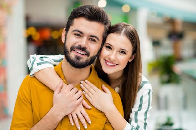 Nahaufnahmefoto von charmanter hübscher dame, gutaussehendem mannpaar, das freizeit-einkaufszentrum-wochenende umarmt, huckepack posiert und fotografiert, lässiges jeanshemd-outfit drinnen trägt