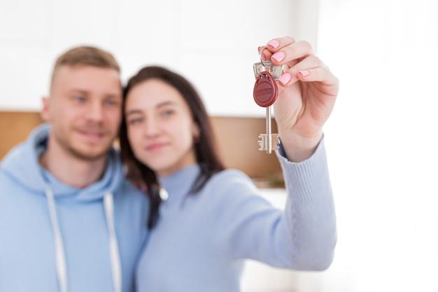 Nahaufnahmefoto von dornen von der wohnungstür, eine frau, die die schlüssel zu einer neuen wohnung hält