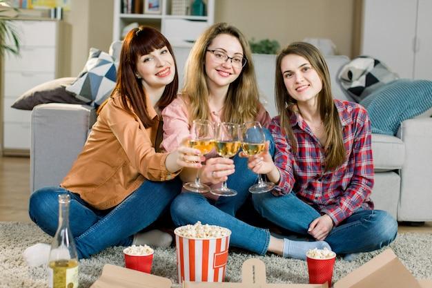 Nahaufnahmefoto von drei fröhlichen lächelnden mädchen, die eine party zu hause feiern und weißwein mit pizza trinken. feier, freundschaftskonzept
