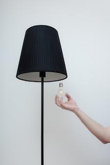Nahaufnahmefoto von eine hand ändert eine glühbirne in einer stilvollen loftlampe