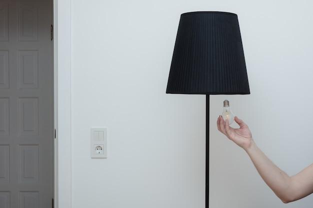 Nahaufnahmefoto von eine hand wechselt eine glühbirne in einer stilvollen loftlampe von der unterseite