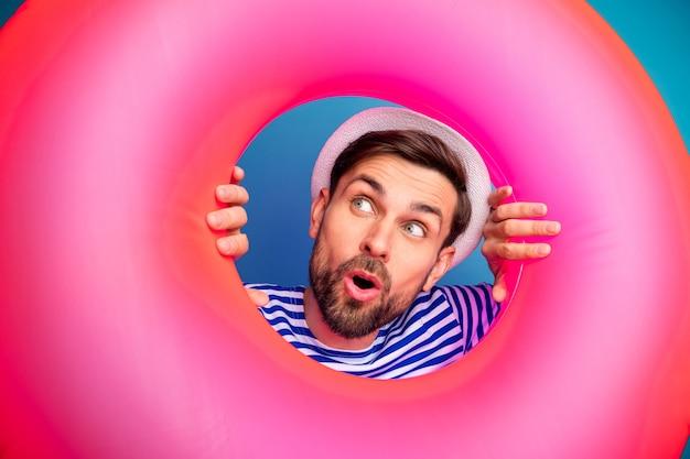 Nahaufnahmefoto von funky aufgeregtem hübschem kerl touristenblick in buntem rosa gummi-rettungsring sehen niedrige preise einkaufen tragen gestreifte matrosenhemdkappe isolierte blaue farbe