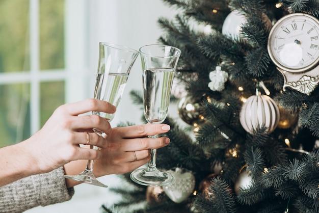 Nahaufnahmefoto von gläsern champagner in den händen gegen einen hintergrund des weihnachtsbaums