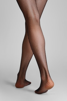 Nahaufnahmefoto von langen dünnen weiblichen beinen in den schwarzen fischnetzstrumpfhosen. rückansicht, geh weg