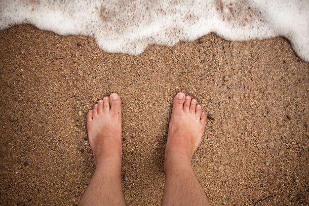 Nahaufnahmefoto von männlichen füßen, die am sandstrand stehen
