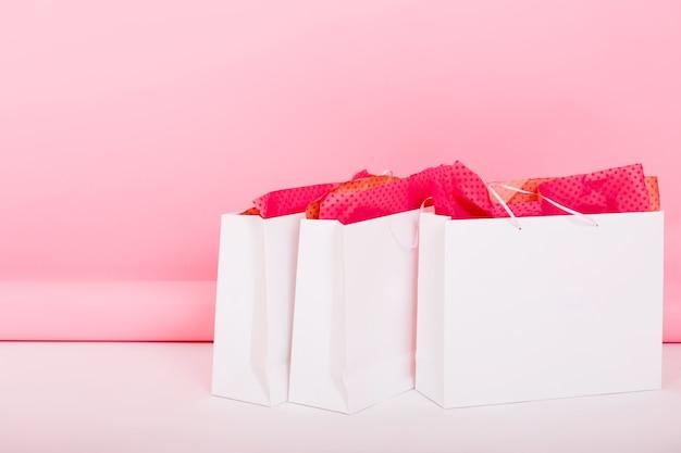 Nahaufnahmefoto von niedlichen geschenktüten mit geschenkpapier, das auf dem boden auf rosa hintergrund liegt. jemand hat seine einkäufe in weißen paketen für ein geburtstagsgeschenk hinterlassen, nachdem er im zimmer eingekauft hatte.