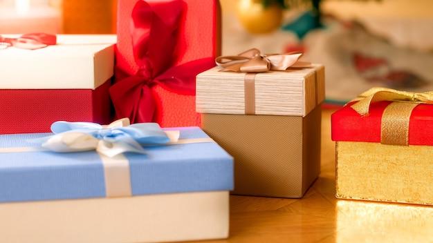 Nahaufnahmefoto von schönen kisten für geschenke oder geschenke mit bändern und schleifen, die auf holzboden im wohnzimmer liegen. perfekter abstrakter hintergrund für feiertage oder feiern