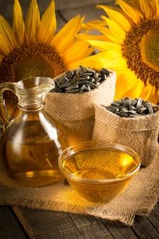Nahaufnahmefoto von sonnenblumenöl mit samen auf hölzernem hintergrund. bio- und bio-produktkonzept.