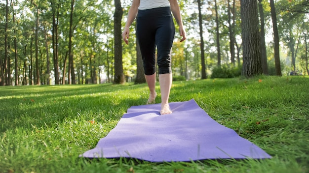 Nahaufnahmefoto von weiblichen füßen, die auf der fitnessmatte gehen, die auf gras im park liegt. frau macht yoga-übungen in der natur