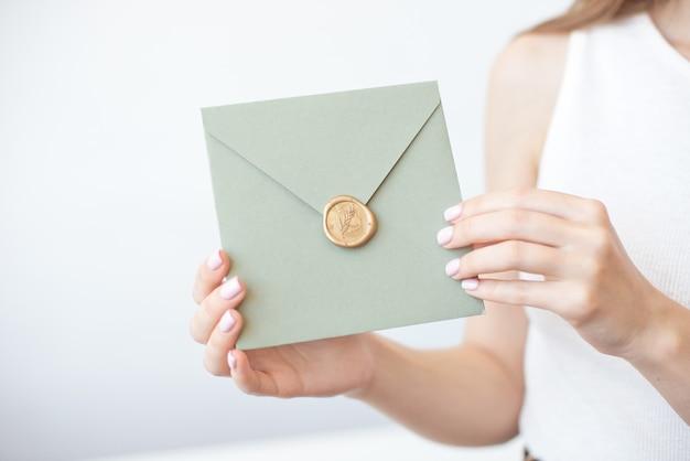 Nahaufnahmefoto von weiblichen händen, die einen silbernen blauen oder rosa einladungsumschlag mit einem wachssiegel, einem geschenkgutschein, einer postkarte, einer hochzeitseinladungskarte halten.