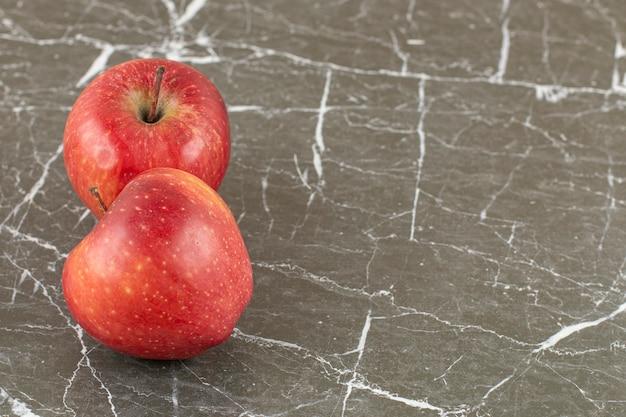 Nahaufnahmefoto von zwei frischen äpfeln auf grauem stein.