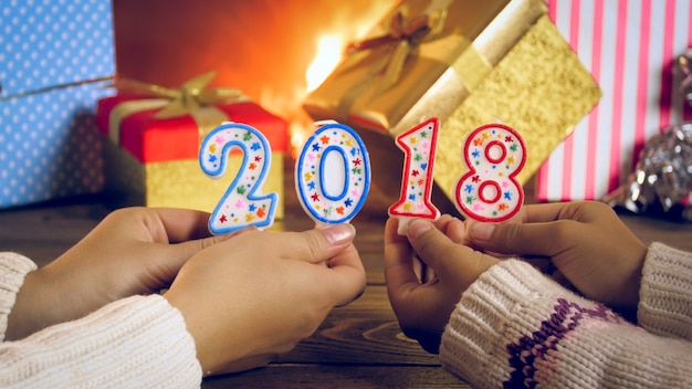 Nahaufnahmefoto von zwei mädchen, die 2018 zahlen neben brennendem kamin und bunten weihnachtsgeschenken halten