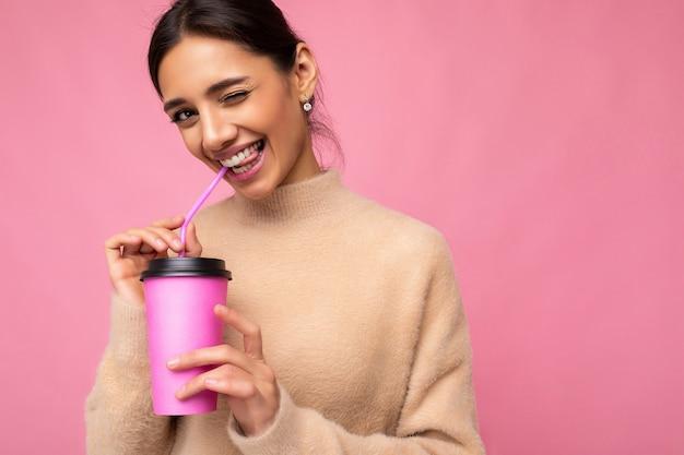 Nahaufnahmefotoaufnahme der schönen jungen brünettenfrau, die beige pullover lokalisiert über rosa hintergrund hält, hält papierkaffeetasse für modell trinken und kamera betrachten und zwinkert. freiraum