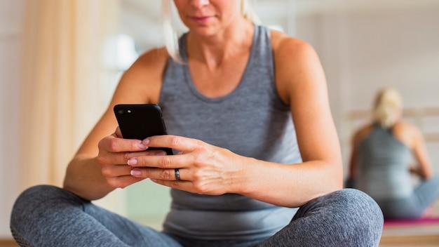 Nahaufnahmefrau an der sportkleidung telefon überprüfend