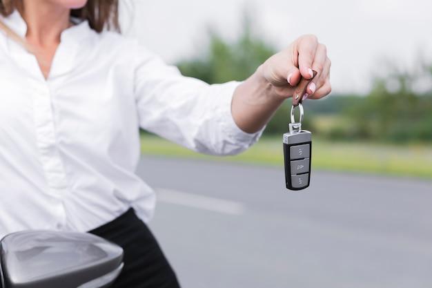 Nahaufnahmefrau, die autoschlüssel hält
