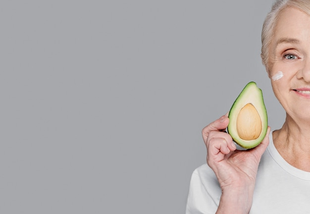 Nahaufnahmefrau, die avocado mit kopienraum hält