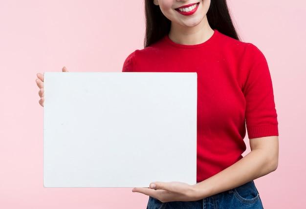 Nahaufnahmefrau, die blatt des leeren papiers hält