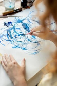 Nahaufnahmefrau, die blaue farbe verwendet