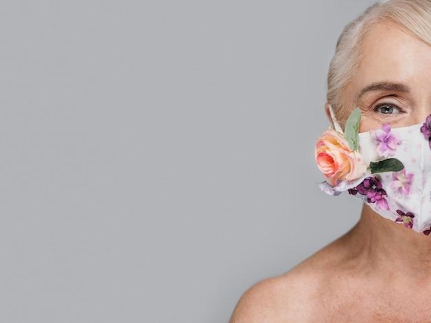 Nahaufnahmefrau, die blumenmaske mit kopienraum hält