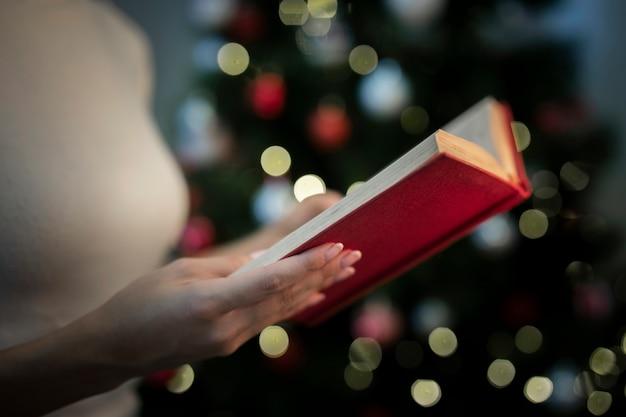 Nahaufnahmefrau, die buch mit geschichten für weihnachten hält