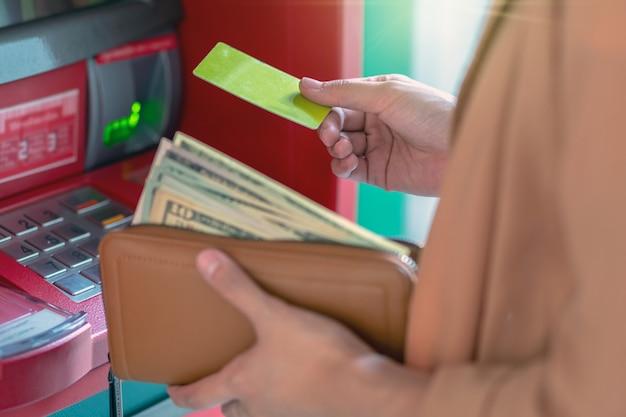 Nahaufnahmefrau, die das bargeld über atm, geschäft geldautomat-konzept zurückzieht