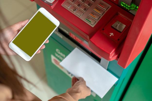 Nahaufnahmefrau, die den intelligenten handy für das abheben des bargeldes und das scannen des barcodes verwendet