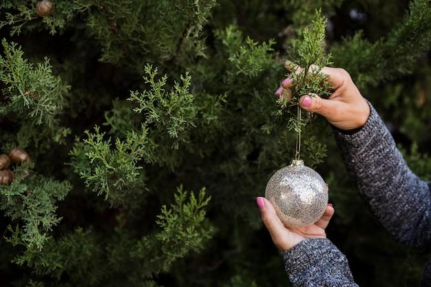 Nahaufnahmefrau, die den weihnachtsbaum mit kugel verziert