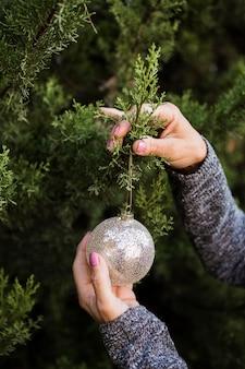 Nahaufnahmefrau, die den weihnachtsbaum verziert