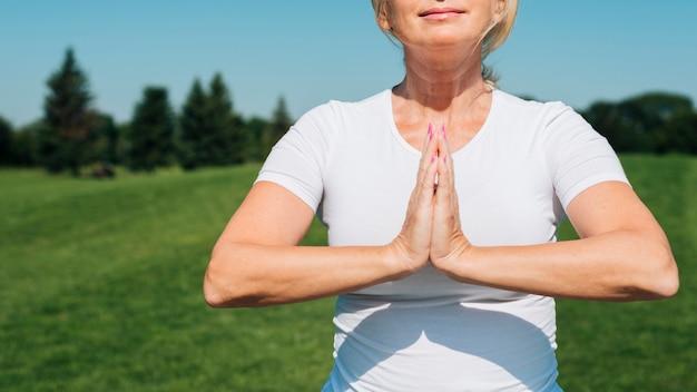Nahaufnahmefrau, die draußen meditiert