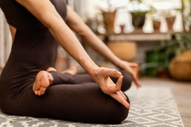 Nahaufnahmefrau, die drinnen meditiert