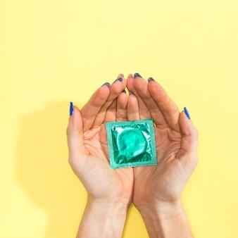 Nahaufnahmefrau, die ein eingewickeltes grünes kondom hält