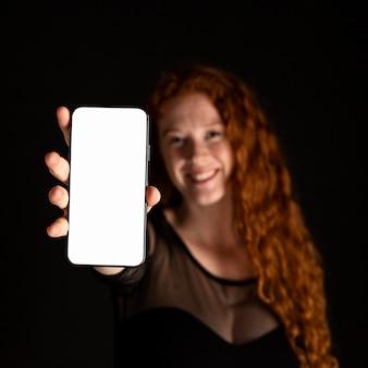 Nahaufnahmefrau, die ein mobiltelefon hält