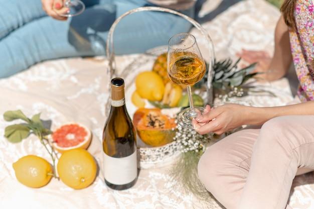Nahaufnahmefrau, die ein weinglas mit weißwein hält. flasche und tropische früchte im hintergrund. frauen sitzen auf einer decke und haben picknick.