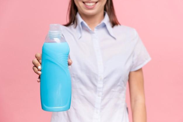 Nahaufnahmefrau, die eine flasche blaues reinigungsmittel hält