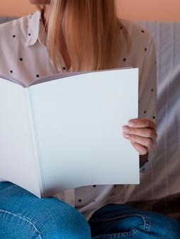 Nahaufnahmefrau, die eine modellzeitschrift hält