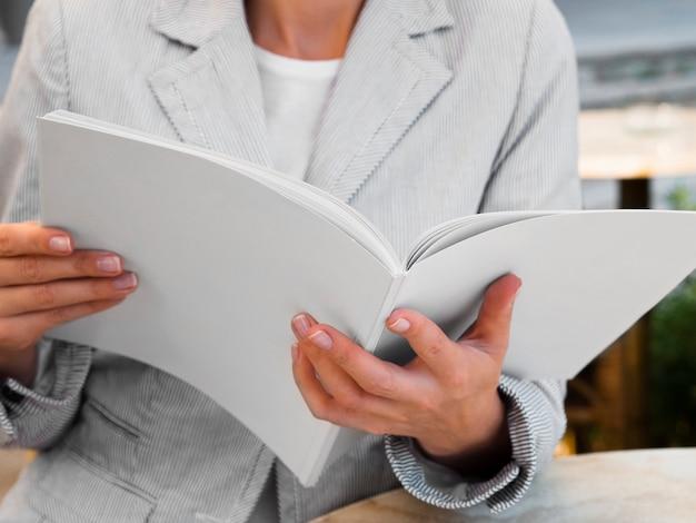 Nahaufnahmefrau, die eine modellzeitschrift liest