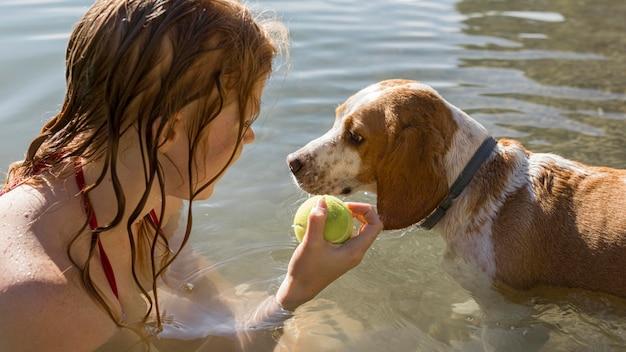 Nahaufnahmefrau, die einen ball für ihren hund hält