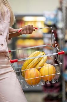 Nahaufnahmefrau, die einkaufswagen mit früchten trägt