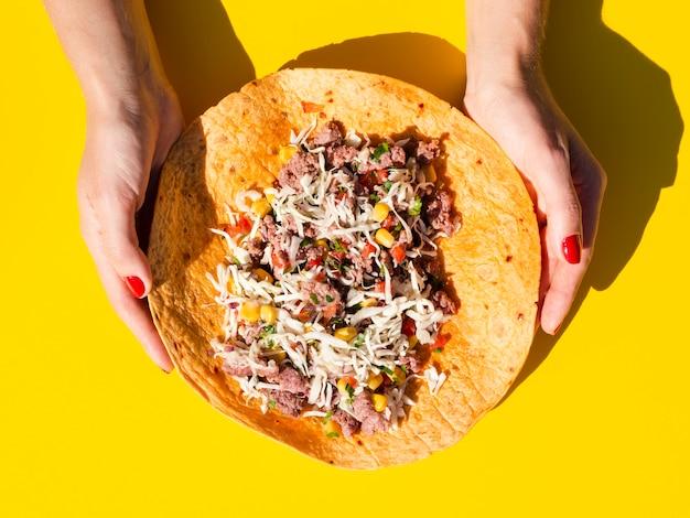 Nahaufnahmefrau, die entfalteten burrito hält