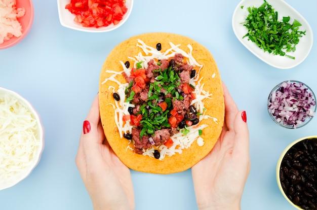 Nahaufnahmefrau, die entfalteten burrito mit blauem hintergrund hält