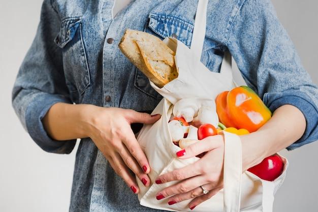 Nahaufnahmefrau, die frische und organische produkte hält