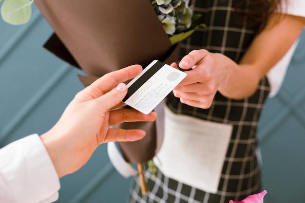 Nahaufnahmefrau, die für blumenstrauß mit kreditkarte zahlt