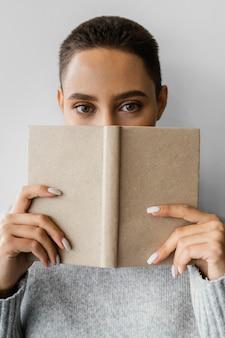 Nahaufnahmefrau, die gesicht mit notizbuch bedeckt