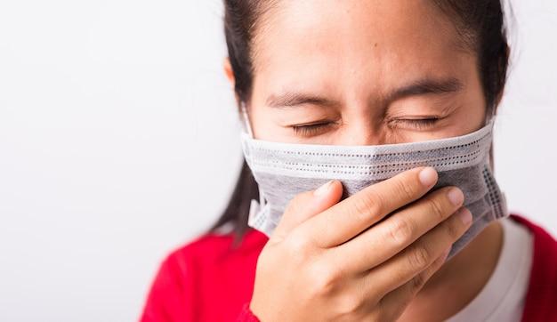Nahaufnahmefrau, die gesichtsmaske trägt, die gegen coronavirus oder covid-19 schützt